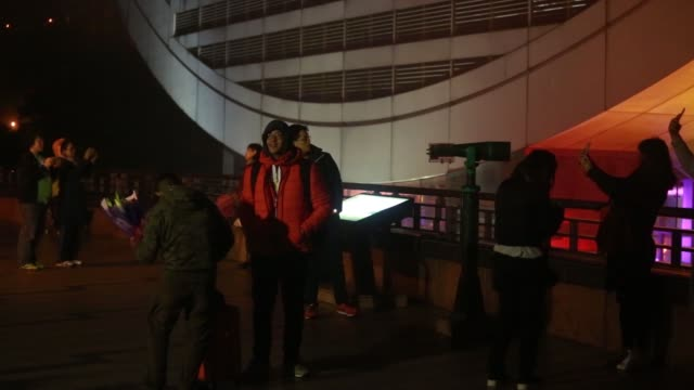 a man takes a selfie in front of the peak tower shrouded in mist at dusk on victoria peak in hong kong china on friday jan 22 pedestrians walk past... - victoria peak stock videos & royalty-free footage