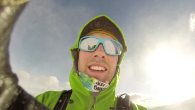 a man takes a selfie while skiing. - slow motion - sportkleidung stock-videos und b-roll-filmmaterial