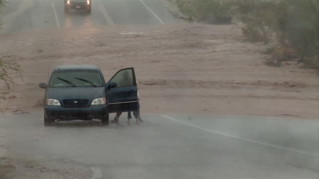A man takes children out of a stopped minivan on a flooded road and puts them into an SUV, then runs back to his minivan and drives away from the flood.