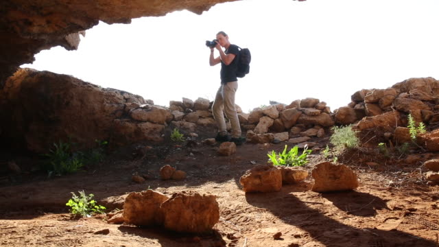stockvideo's en b-roll-footage met man takes dslr video of cave interior, opening - repubiek cyprus