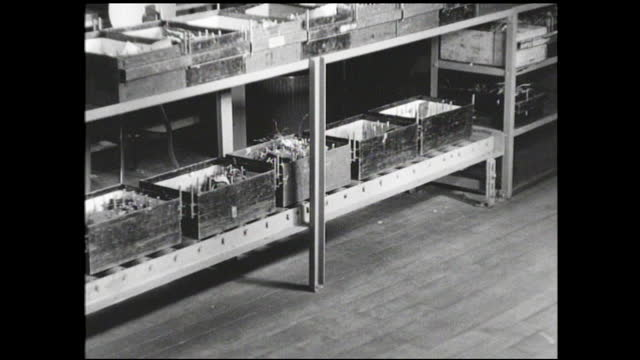 man takes file card and moves bin full of parts along the conveyor belt; man empties bin of parts on a woman's workstation; men taking bins off the... - 1940 1949 stock videos & royalty-free footage
