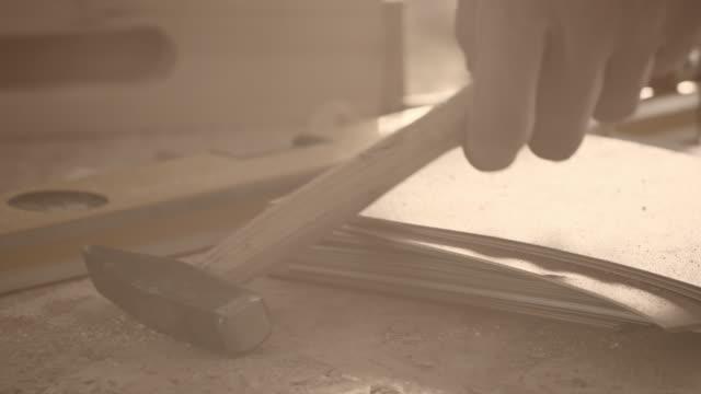 mann nimmt hammer vom tisch in workshops - greifen stock-videos und b-roll-filmmaterial