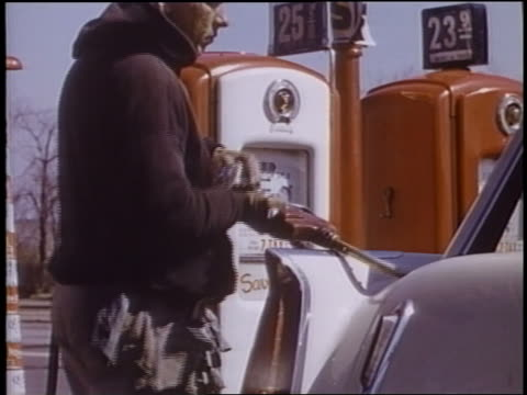 1958 man takes hose from car to pump at gas station - filling station attendant stock videos and b-roll footage