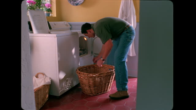 a man takes laundry out of the dryer and places it into a basket. - wäschekorb stock-videos und b-roll-filmmaterial