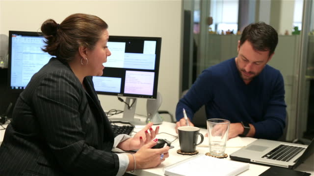 Man takes notes from female boss in small private corporate office