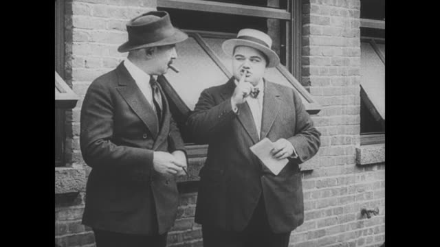 1917 man (fatty arbuckle) takes notes on overhead racing tips before confidently placing a bet - 可能性点の映像素材/bロール