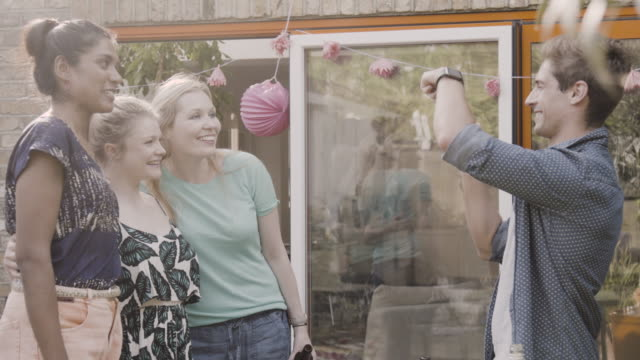 Man takes photo of friends at garden party, they look at the results, laughing.