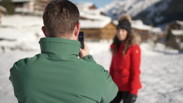 vídeos de stock e filmes b-roll de a man takes photographs of his wife, lifestyle in the snow at a ski resort. - casaco de esqui