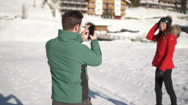 a man takes photographs of his wife, lifestyle in the snow at a ski resort. - photography stock-videos und b-roll-filmmaterial