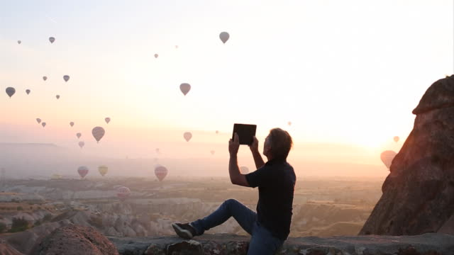 Man takes pic as balloons rise above desert landscape