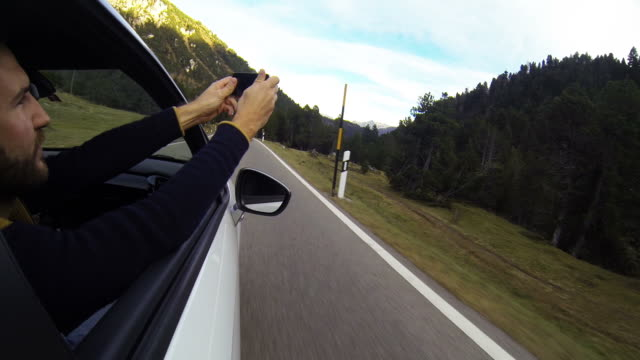 Man takes picture from moving car using a smartphone