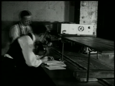 vídeos de stock e filmes b-roll de b/w 1929 man takes radio part from conveyor belt as other man writes on clipboard in factory - 1920 1929