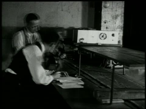 vídeos y material grabado en eventos de stock de b/w 1929 man takes radio part from conveyor belt as other man writes on clipboard in factory - 1920 1929