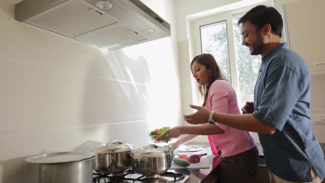 MS Man takes salad bowl from woman in kitchen / India