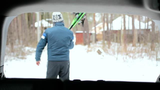 vídeos de stock, filmes e b-roll de um homem pega esquis do porta-malas de um carro. - equipamento esportivo