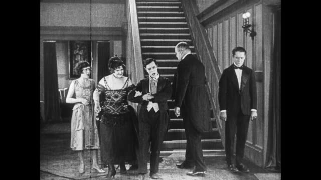 1922 Man (Buster Keaton) takes the arm of rich woman
