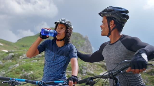 vídeos y material grabado en eventos de stock de hombre tomando un descanso en su bicicleta y esperando a su hijo en bicicleta por la carretera de montaña - dar