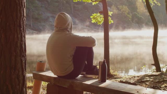 vidéos et rushes de homme prenant une coupure de café à l'extérieur - banc