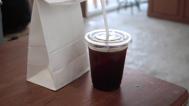 mann nimmt eine tasse kaffee und eine tüte brot im café. - papiertüte stock-videos und b-roll-filmmaterial