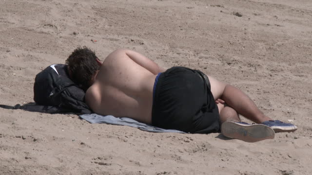 man taking a nap on coney island beach - hot weather - zaino da montagna video stock e b–roll