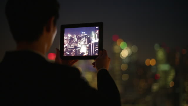 RV Man taking a photo of the city on a digital tablet at night