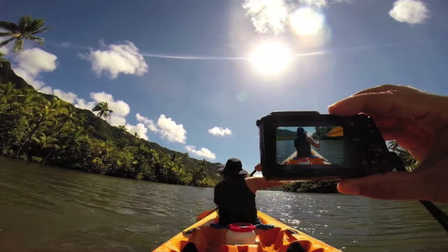 A man taking a picture of a woman kayaking at Raiatea Island on the Faaroa River, the only navigable river in French Polynesia.