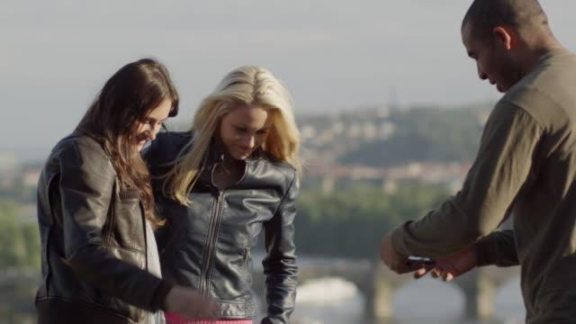 vidéos et rushes de man taking a picture of two women - touriste