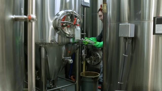 vídeos de stock e filmes b-roll de man taking a sample from a beer fermenter - só um homem de idade mediana