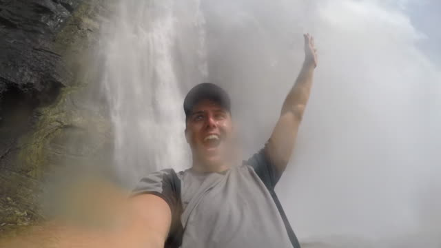 man taking a selfie near emperor falls waterfall robson river on the berg lake trail, mt. robson provincial park. - recreational pursuit stock videos & royalty-free footage