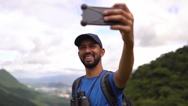 vídeos de stock, filmes e b-roll de homem tirando uma selfie em uma montanha - turista