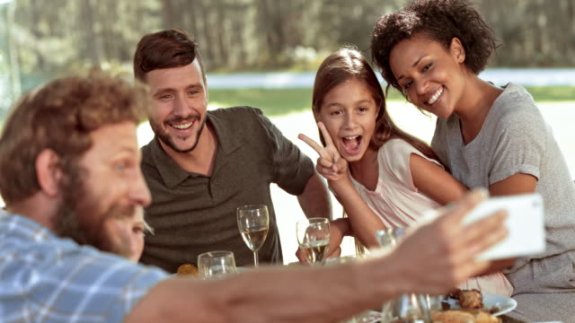 SLO MO Man taking a selfie with his family at the picnic table