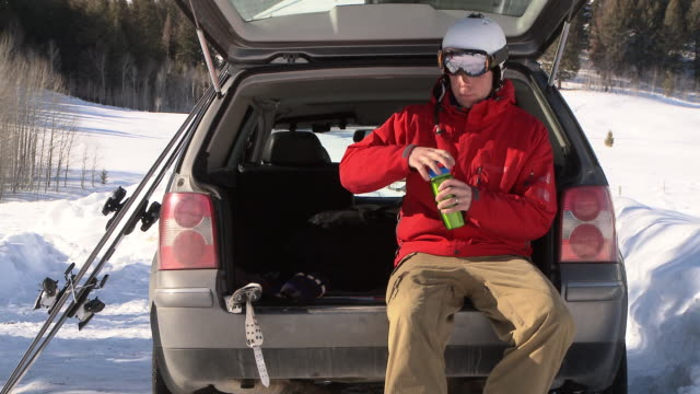 man taking a sip of water and taking off ski boots at back of car / ketchum, idaho, united states - attrezzatura sportiva video stock e b–roll