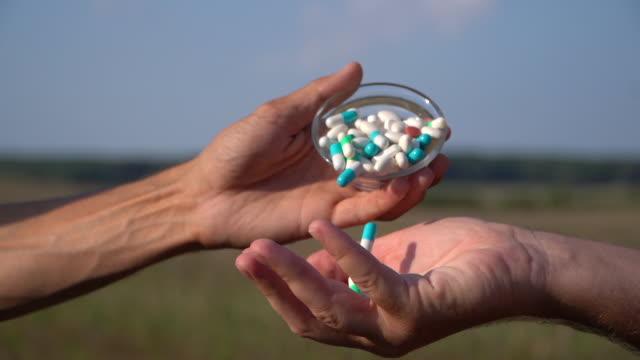man taking aspirin tablet into hand - dissolving stock videos & royalty-free footage