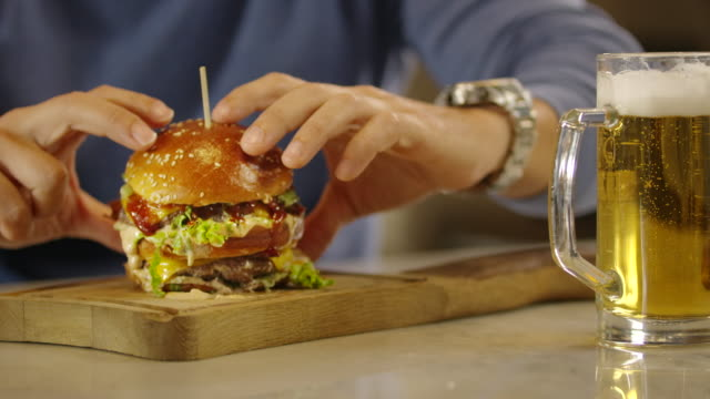 man taking burgers from wooden plate 4k - cheeseburger stock videos & royalty-free footage