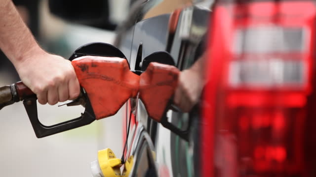 CU of man taking gas nozzle to fill up gas tank