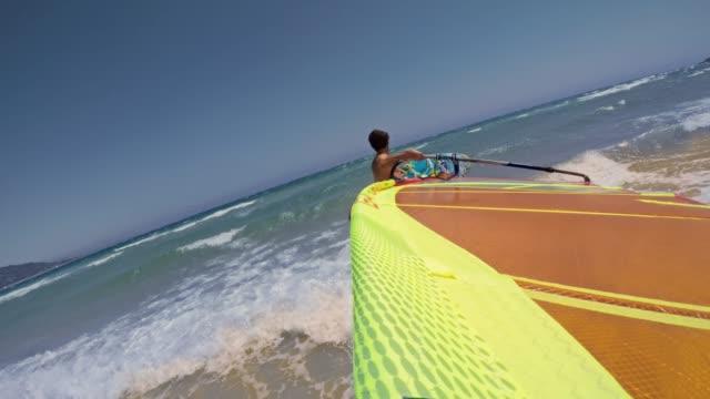pov-mann nimmt seine windsurf ins wasser bei sonnenschein - windsurfen stock-videos und b-roll-filmmaterial