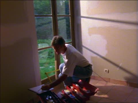 vidéos et rushes de man taking measurements of window of house with tape measure indoors / france - tape measure