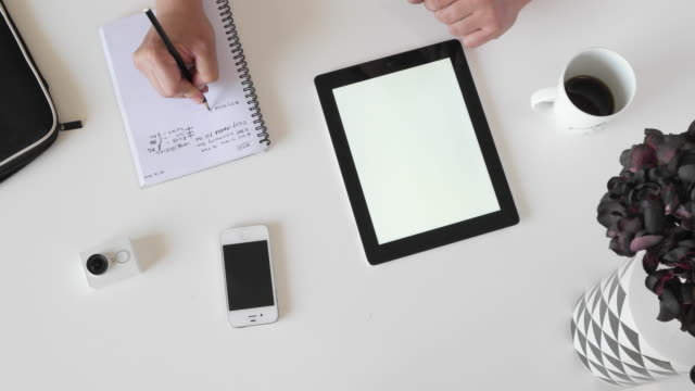 man taking notes on a note pad and explaining on a tablet during a meeting - note pad点の映像素材/bロール
