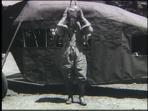B/W man taking off helmet in front of early helicopter (Stratosphere Gyro)