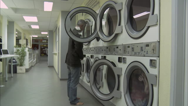 ws man taking off jeans and putting it into washing machine in laundromat / brussels, belgium - launderette stock videos and b-roll footage