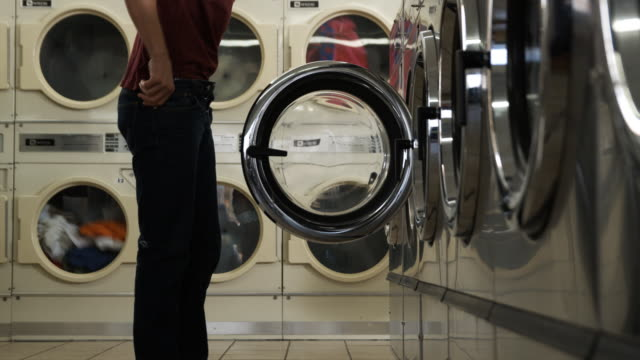 man taking off pants at a laundromat - jeans stock-videos und b-roll-filmmaterial
