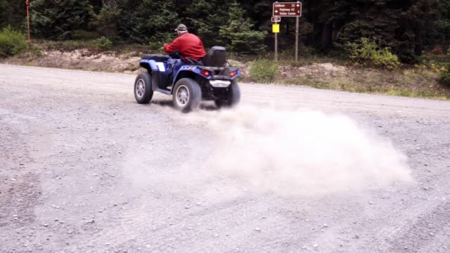 man taking off with a quad, atv or four-wheeler in the forest - off road car stock videos and b-roll footage