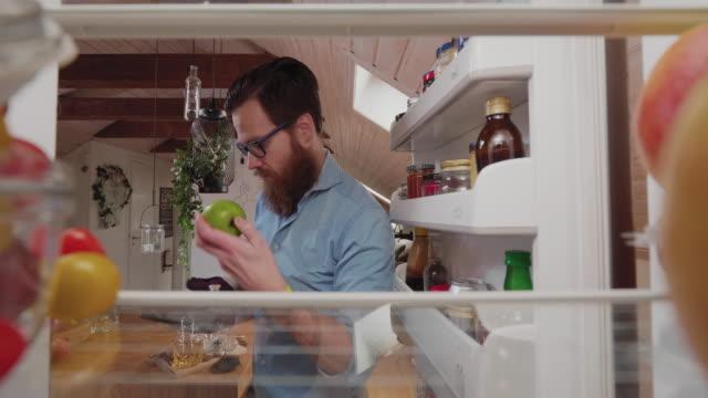 uomo che toglie una mela verde dal frigo - mela video stock e b–roll