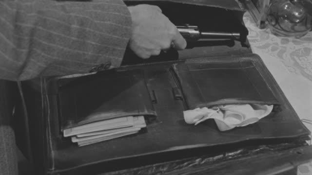 cu man taking out gun from bag - solo un uomo di età media video stock e b–roll