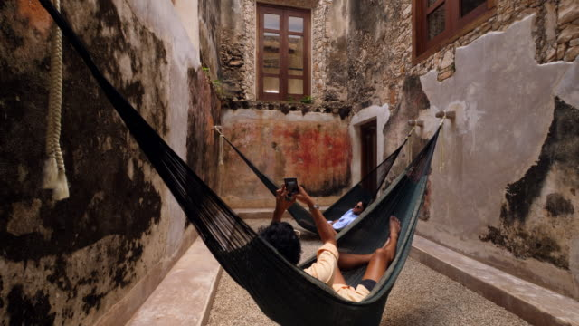 td man taking photo of friend with smartphone while relaxing in hammocks at luxury resort - sitting stock videos & royalty-free footage