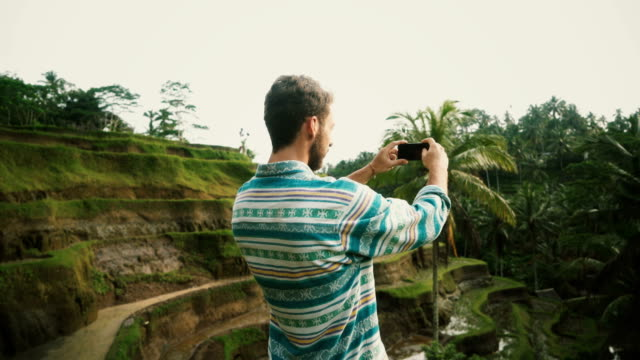 Man taking photo on smartphone Tegallalang rice field in Bali, Indonesia
