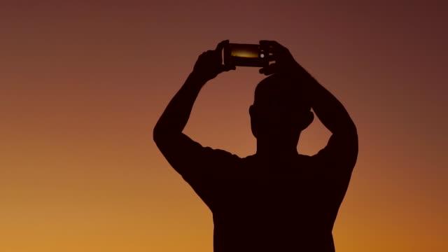 mann, der den sonnenuntergang fotografiert. - fotografie stock-videos und b-roll-filmmaterial