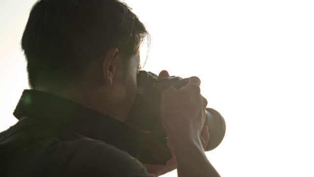 man taking photo with camera at sunset. - photographer stock videos & royalty-free footage