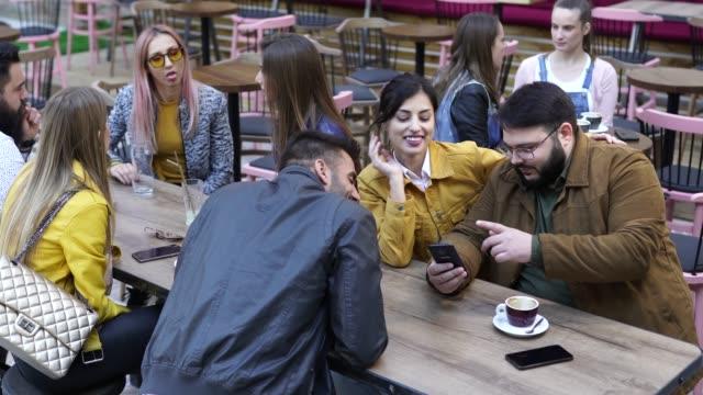 vidéos et rushes de homme prenant la photo avec le téléphone intelligent du couple dans le pub - hipster personne
