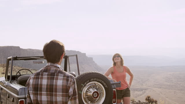 MS Man taking photo with smart phone of smiling girlfriend standing next to convertible off road vehicle on side of desert road overlooking valley